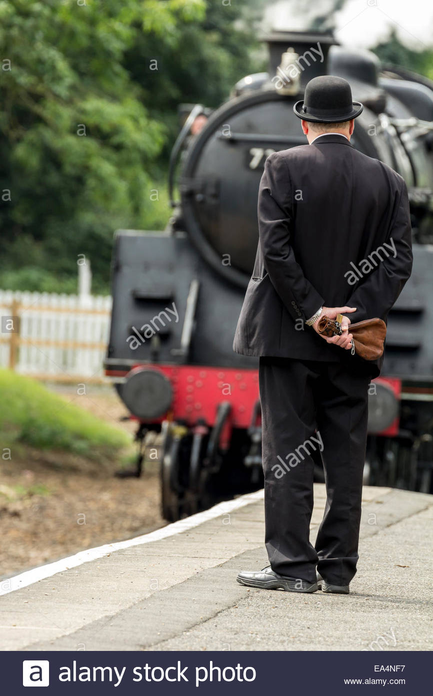 Station Master and approaching train - Stock Image