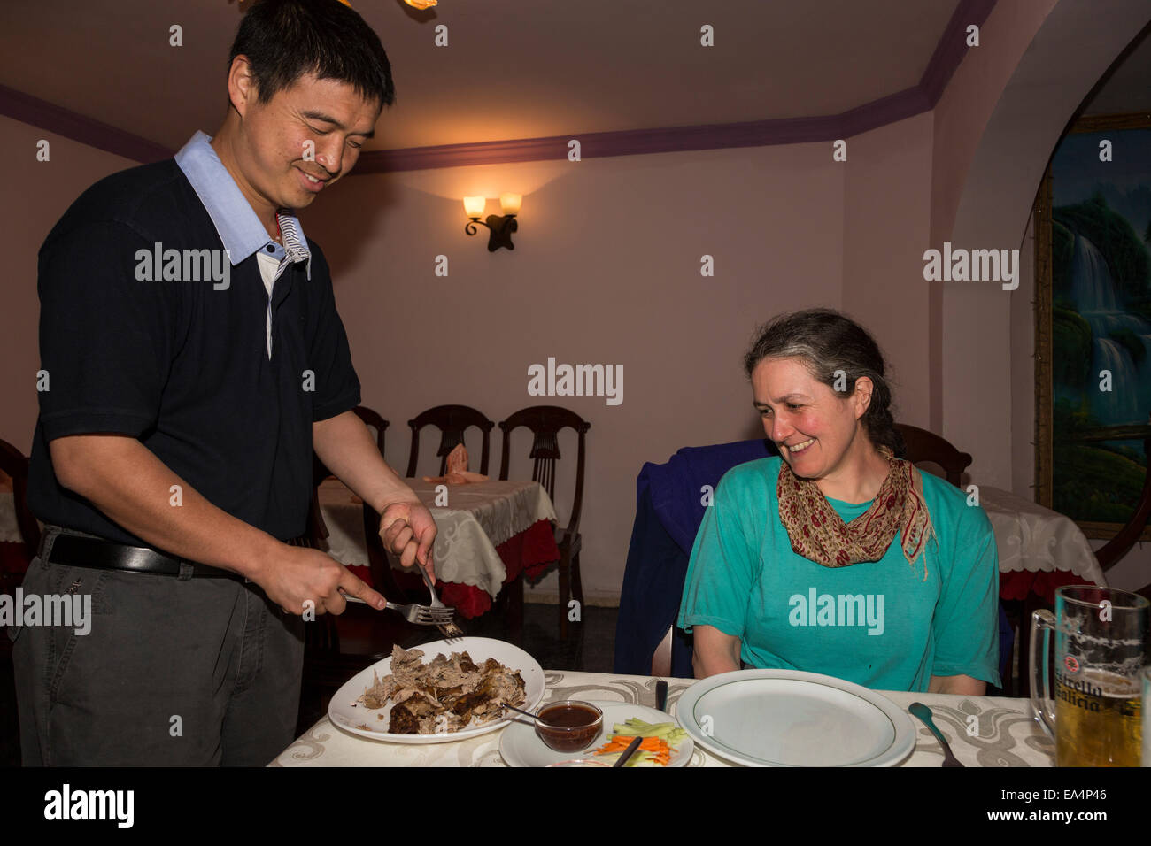 Chinese waiter serving crispy duck to diner in restaurant, Puerto del Carmen, Lanzarote, Canary Islands, Spain - Stock Image