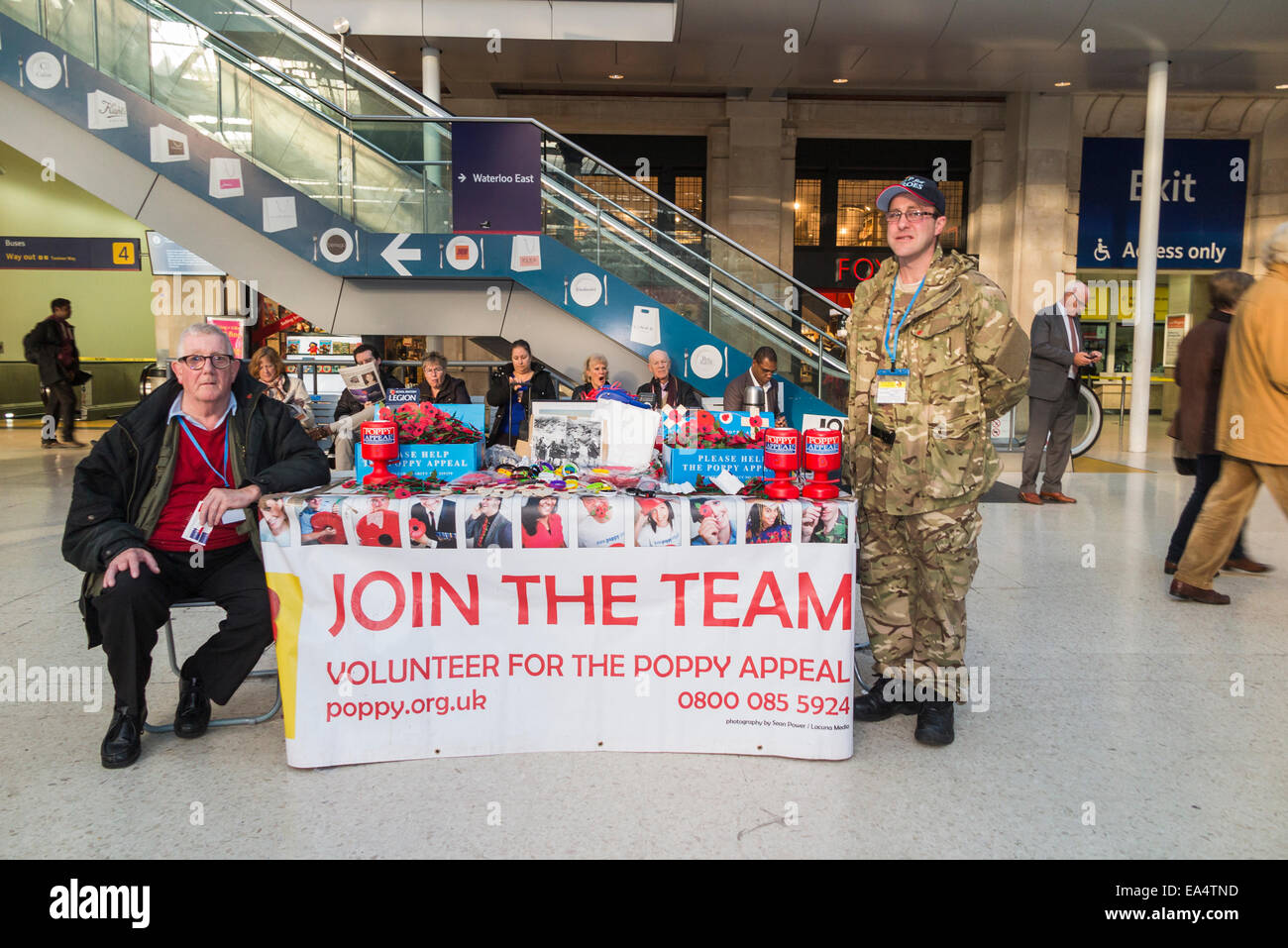 Volunteers selling poppies for the Poppy Appeal for Remembrance Day at a stall in Waterloo Station concourse, London Stock Photo