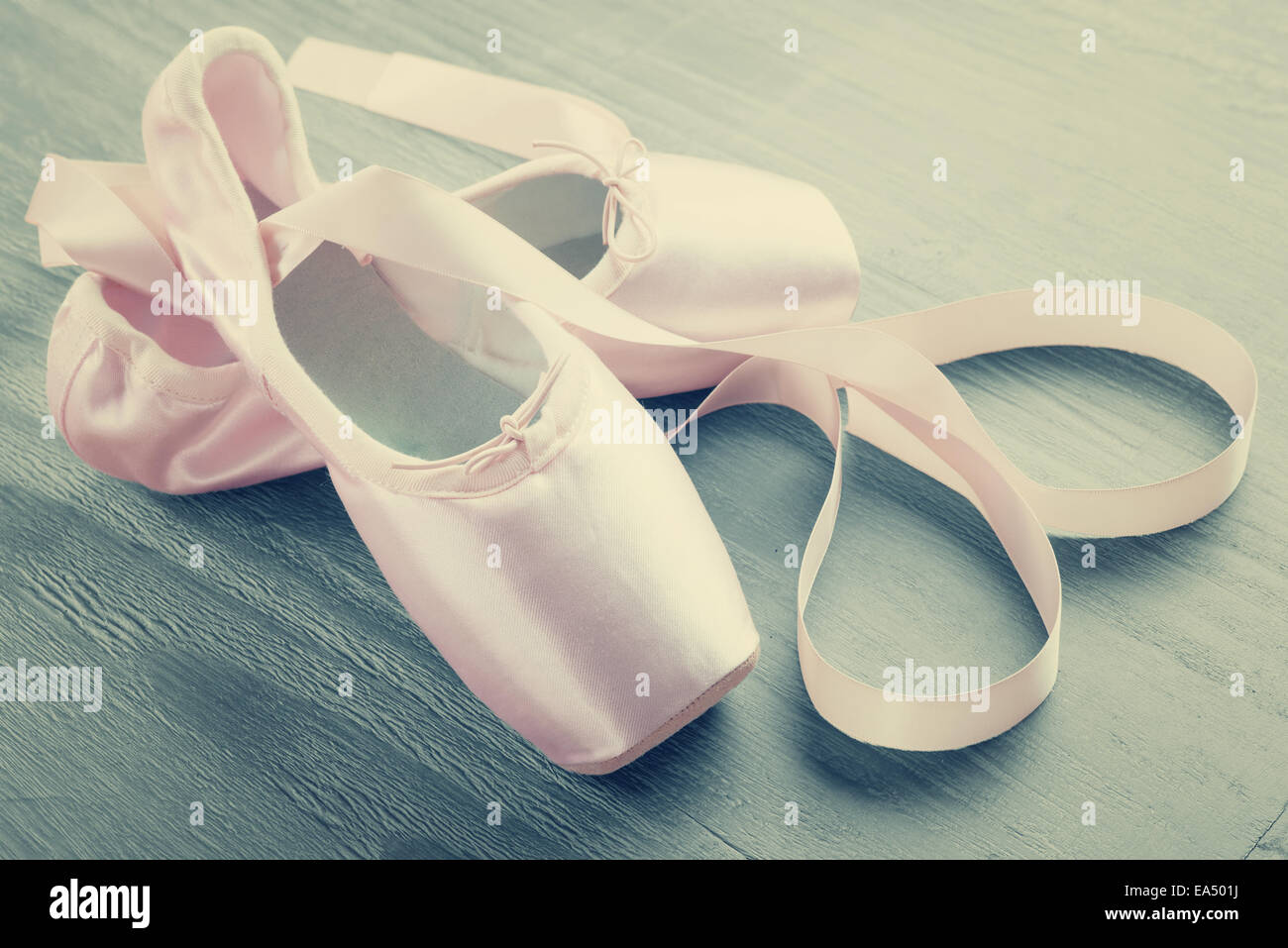 new pink ballet pointe shoes on  wooden background in vintage style - Stock Image