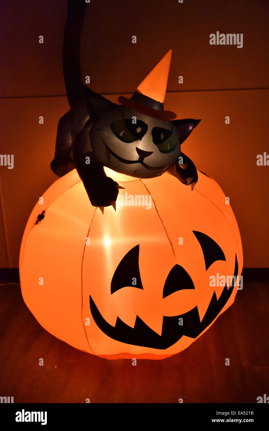 An inflatable halloween pumpkin with a black cat - Stock Image