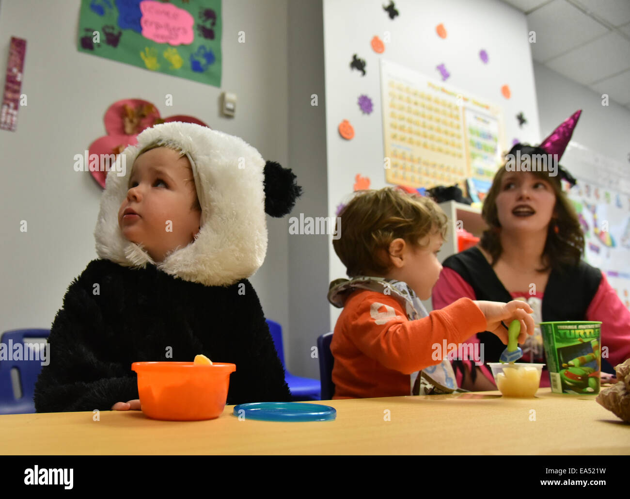 Preschool children with their teacher in fancy dress in their kindergarten classroom at halloween - Stock Image
