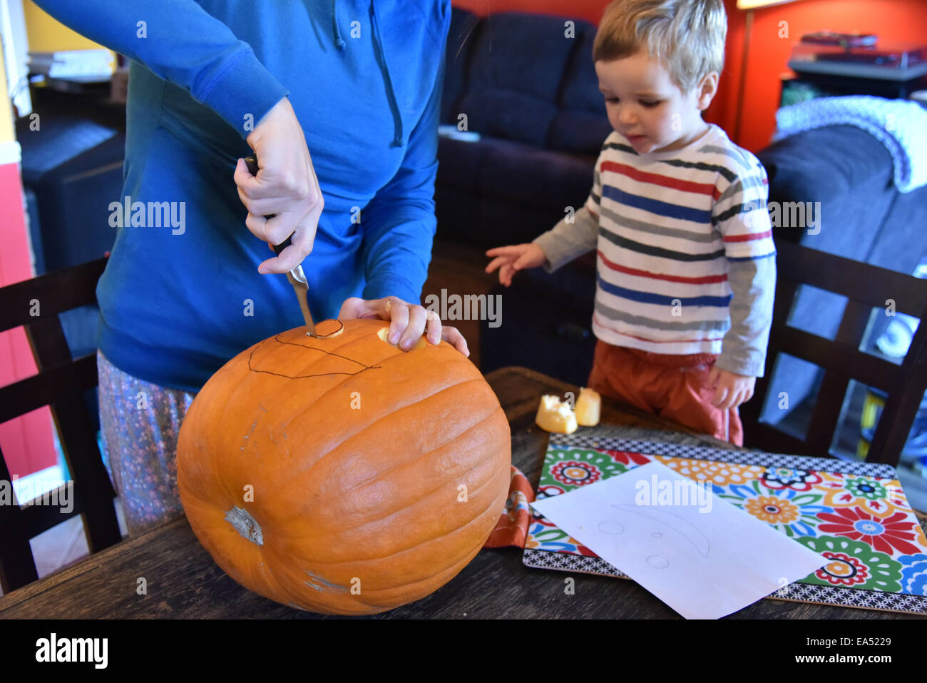 A mother carving a face in a pumpkin while her son watches - Stock Image