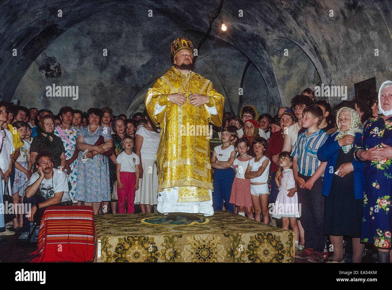 Russian Orthodox priest in Siberia with congregation including many children and older adults. - Stock Image