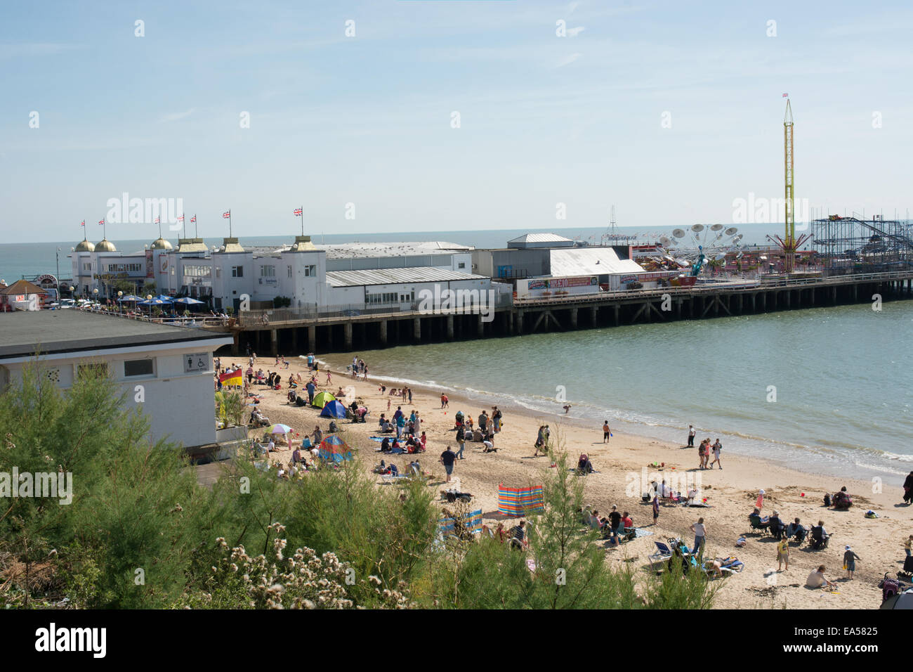 A view from the upper esplanade of Clacton-on-Sea pier and beach on a sunny day. Visitors are enjoying the sandy - Stock Image