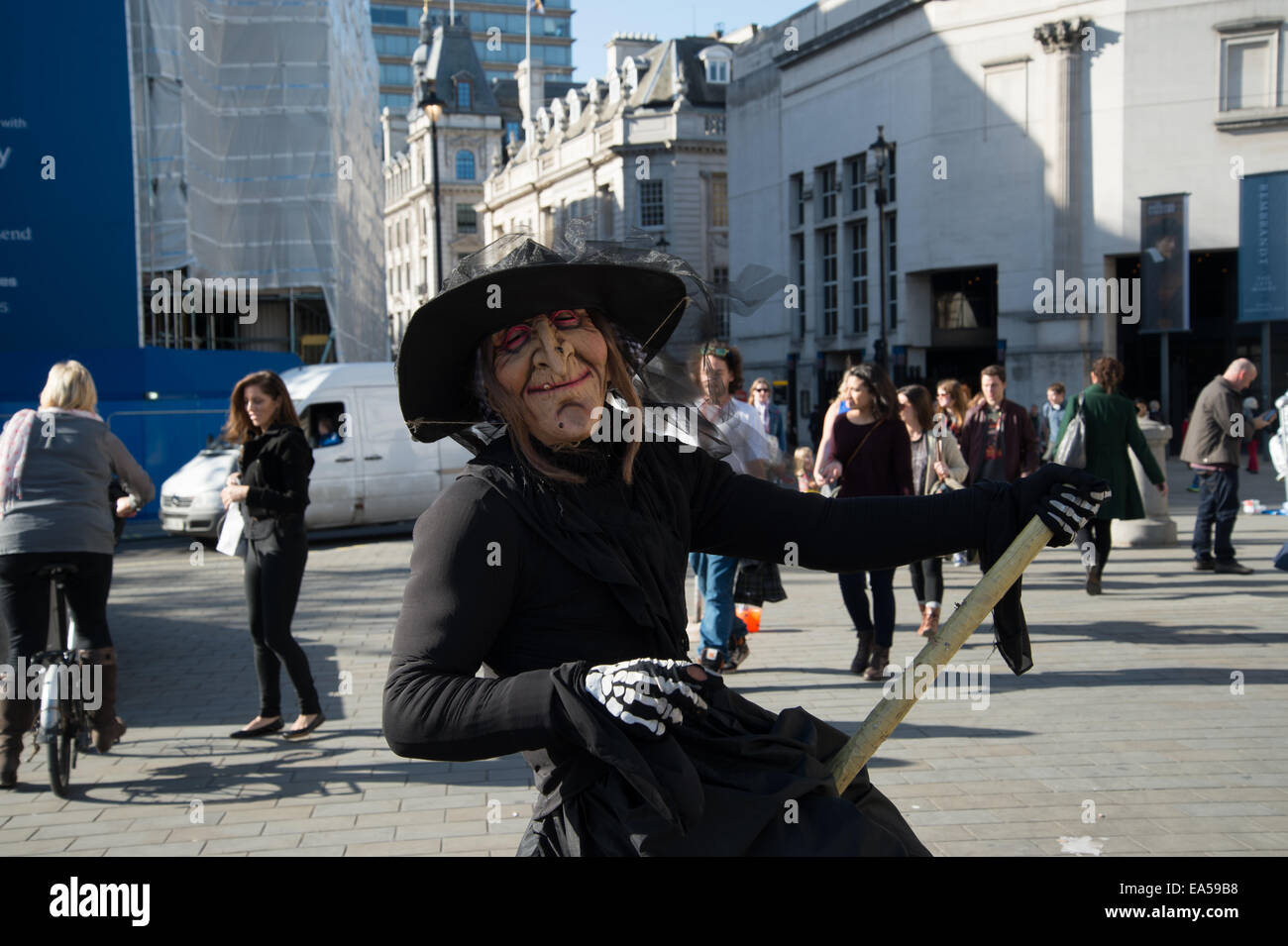 Trafalgar square. A mime artist dressed as a witch appears to be riding a broomstick - Stock Image