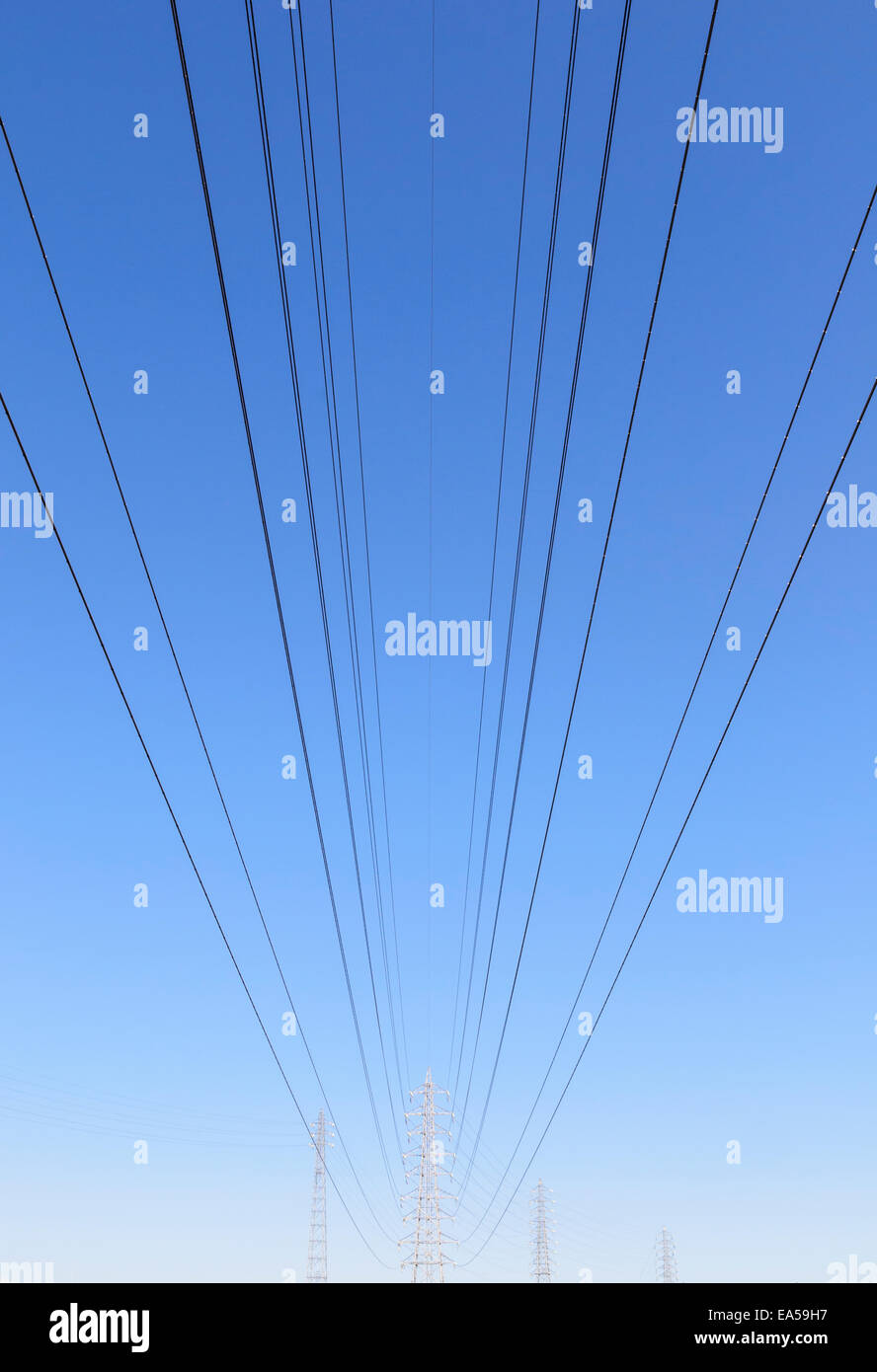 Power lines leading to transmission towers in the distance - Stock Image
