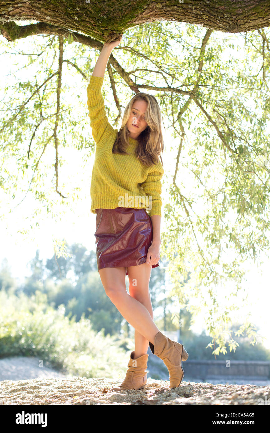 Young woman wearing knit pullover and mini skirt - Stock Image