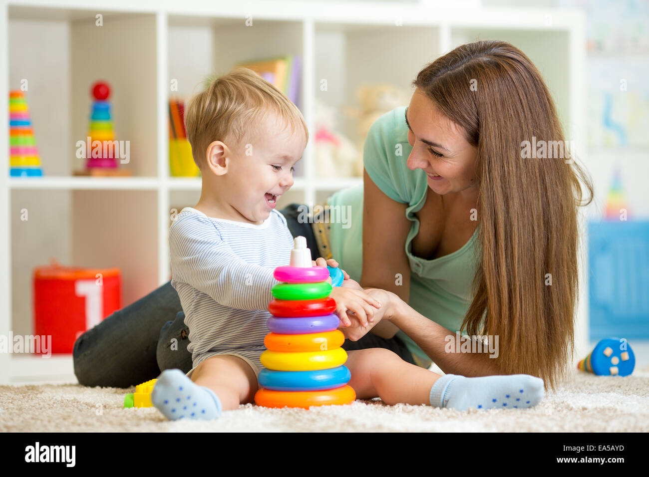 cute mother and child boy play together indoor at home - Stock Image