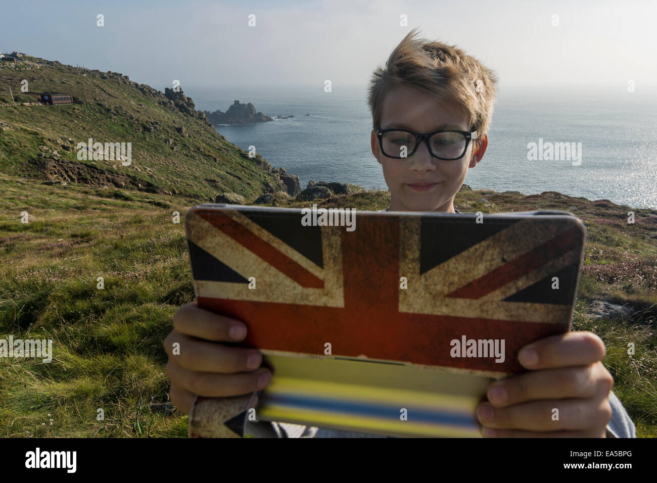 UK, Cornwall, portrait of boy taking a selfie at Land's End with his digital tablet - Stock Image