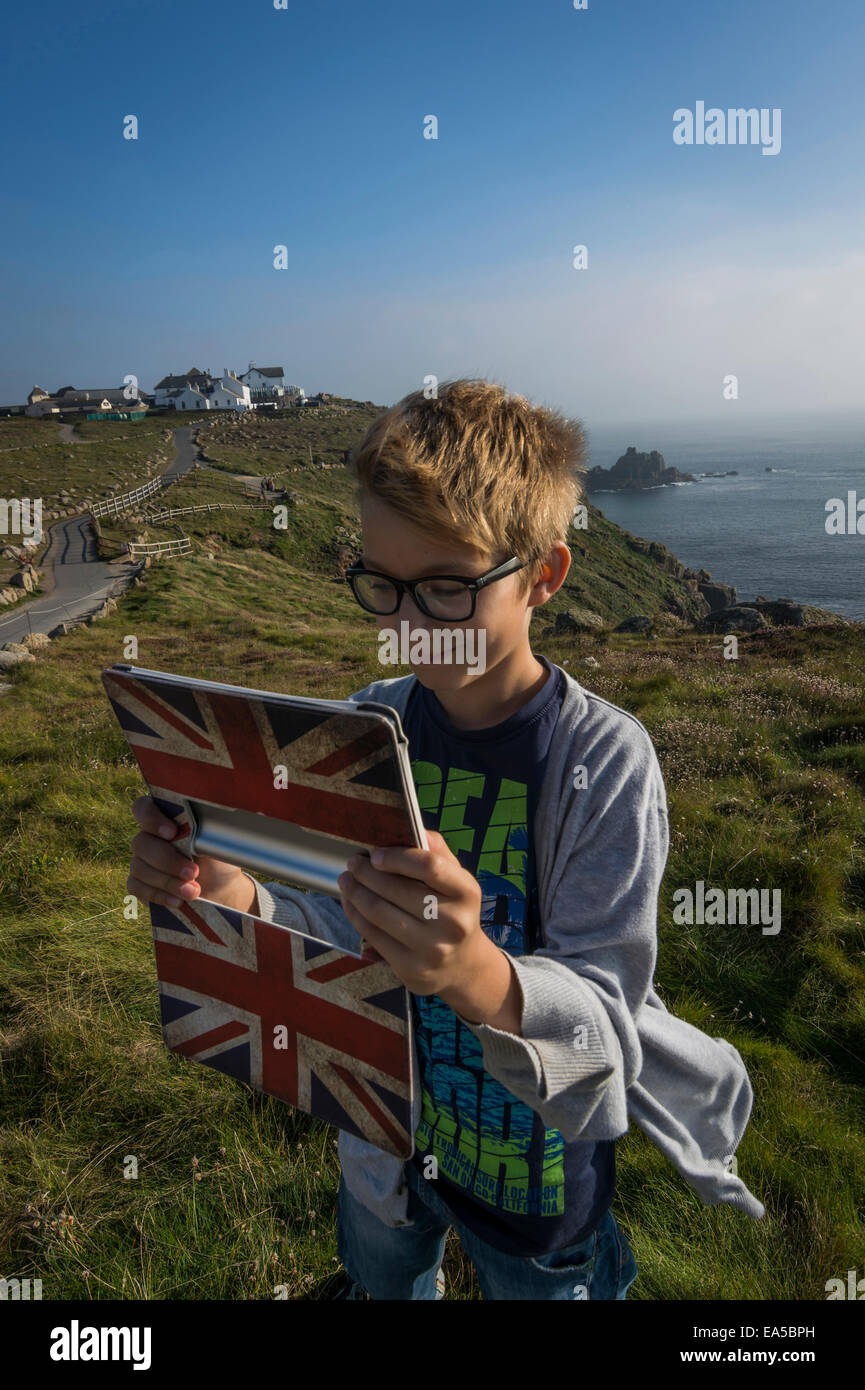 UK, Cornwall, boy taking a selfie at Land's End with his digital tablet - Stock Image