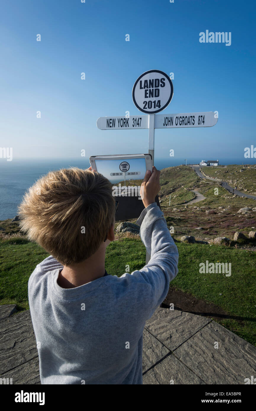 UK, Cornwall, boy photographing direction sign at Land's End with his digital tablet - Stock Image