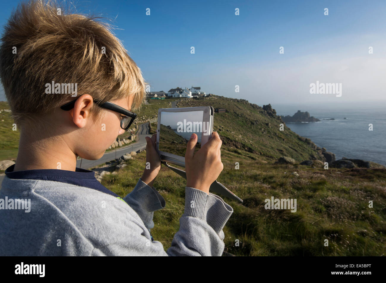 UK, Cornwall, boy photographing landscape at Land's End with his digital tablet - Stock Image