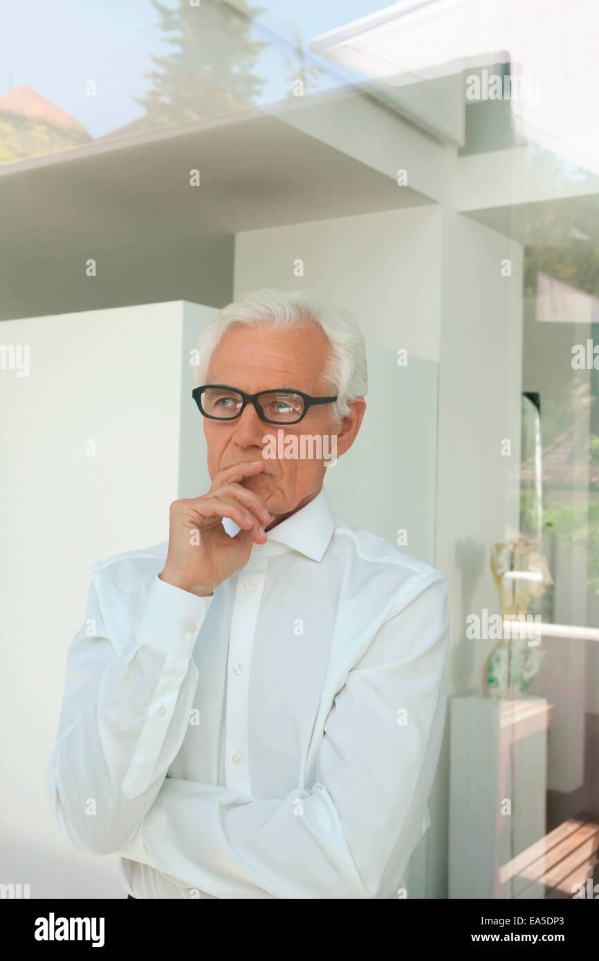 Portrait of pensive senior man looking out of a window - Stock Image