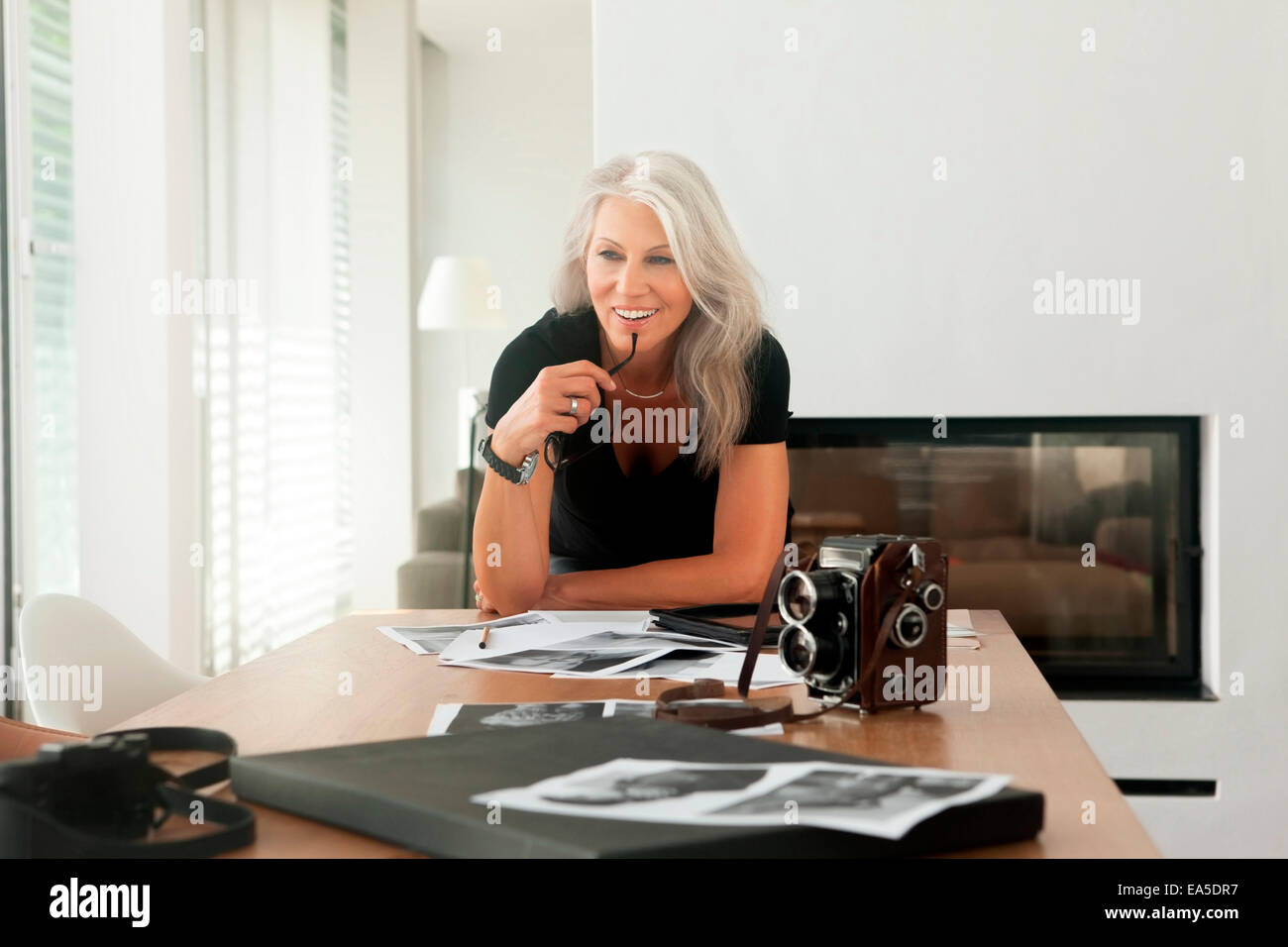 Female photographer with photographs and old fashioned large format camera on a table - Stock Image