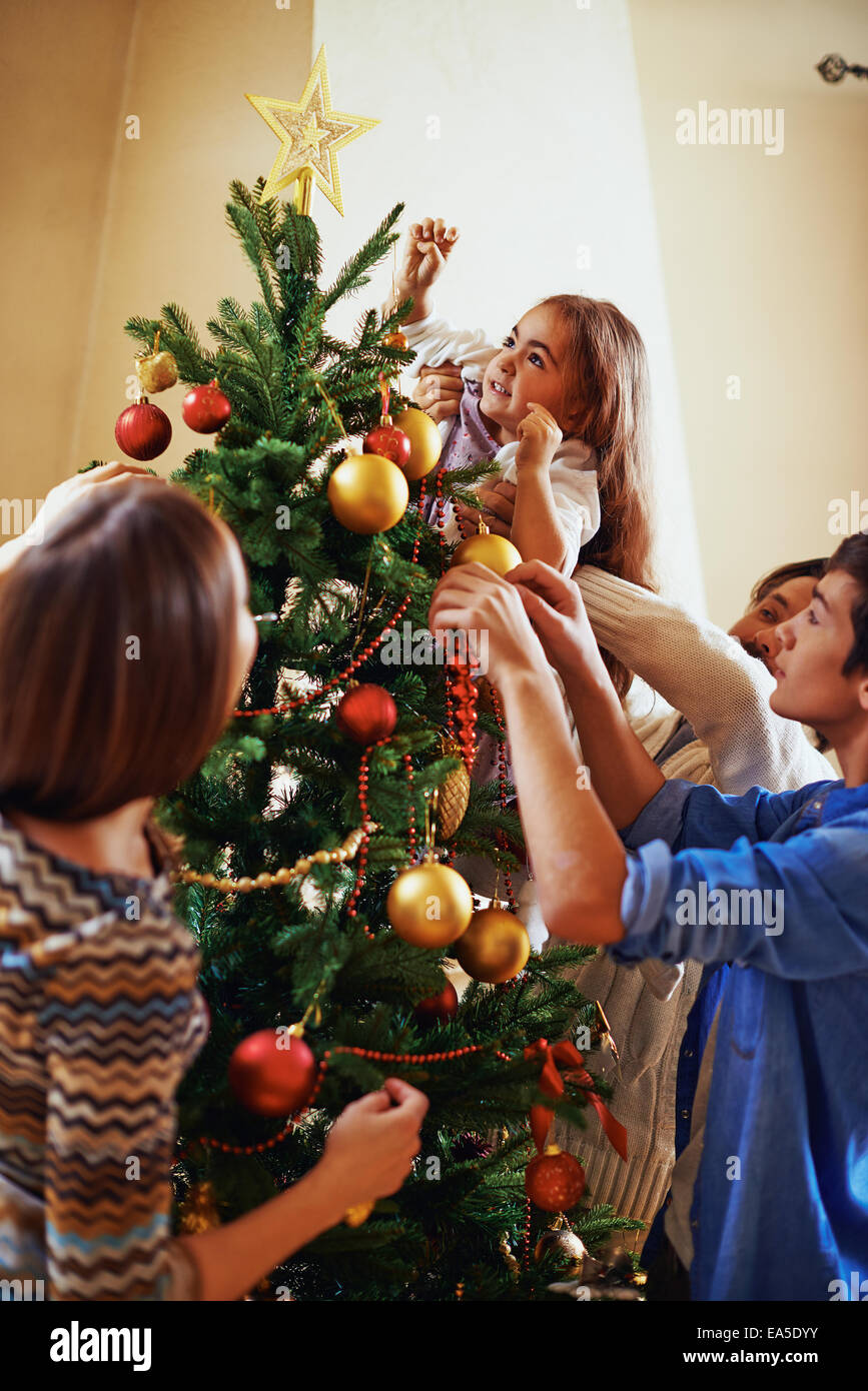 Modern family of four decorating Christmas tree before holiday - Stock Image