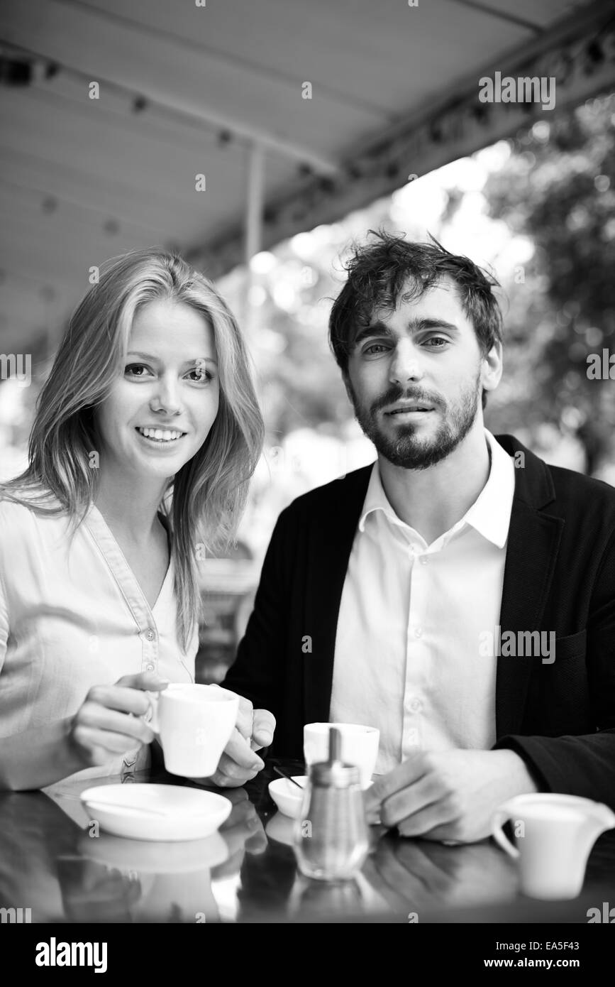 Portrait of calm man and woman having tea or coffee in cafe - Stock Image