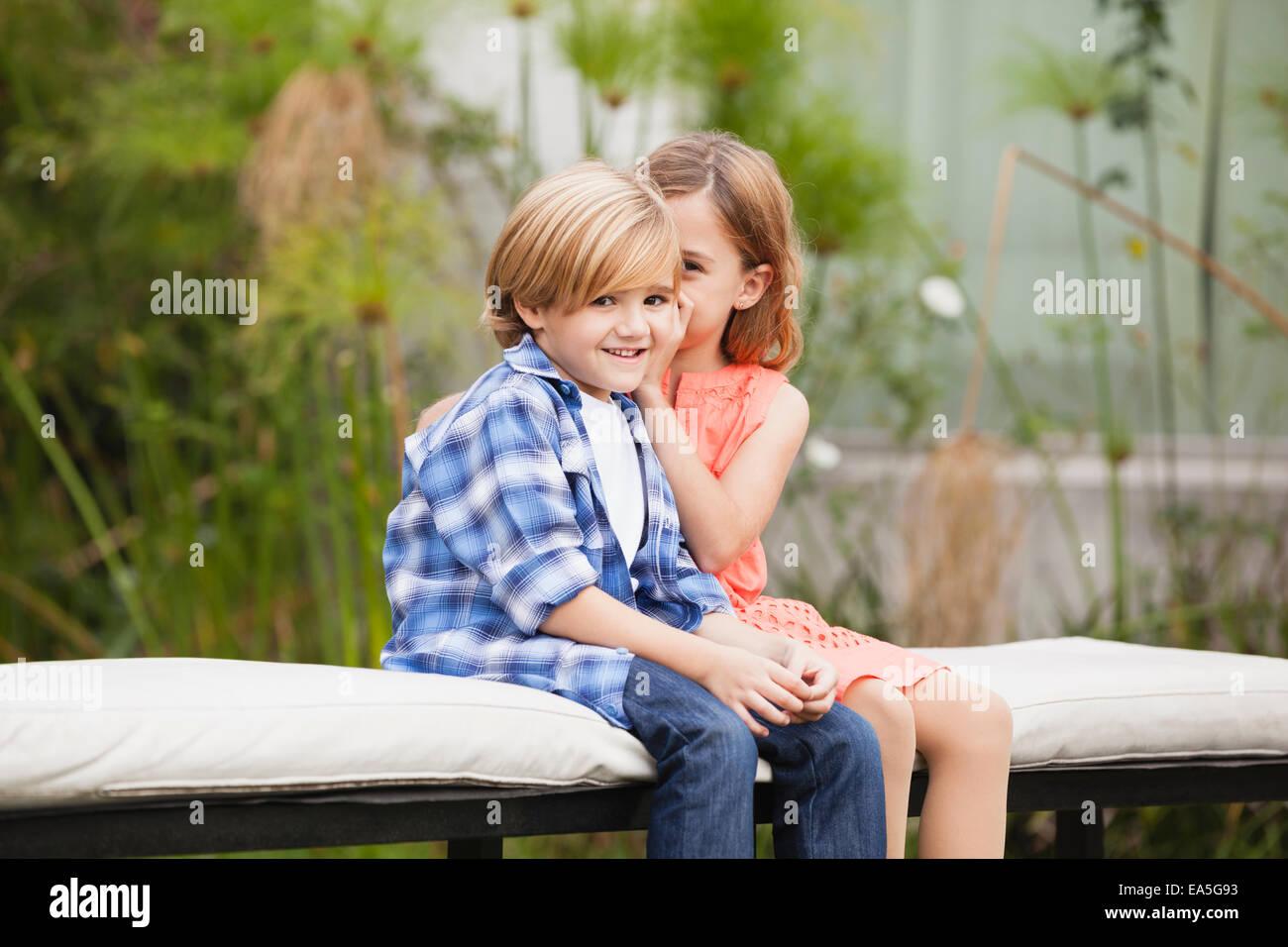Girl whispering into boy's ear - Stock Image