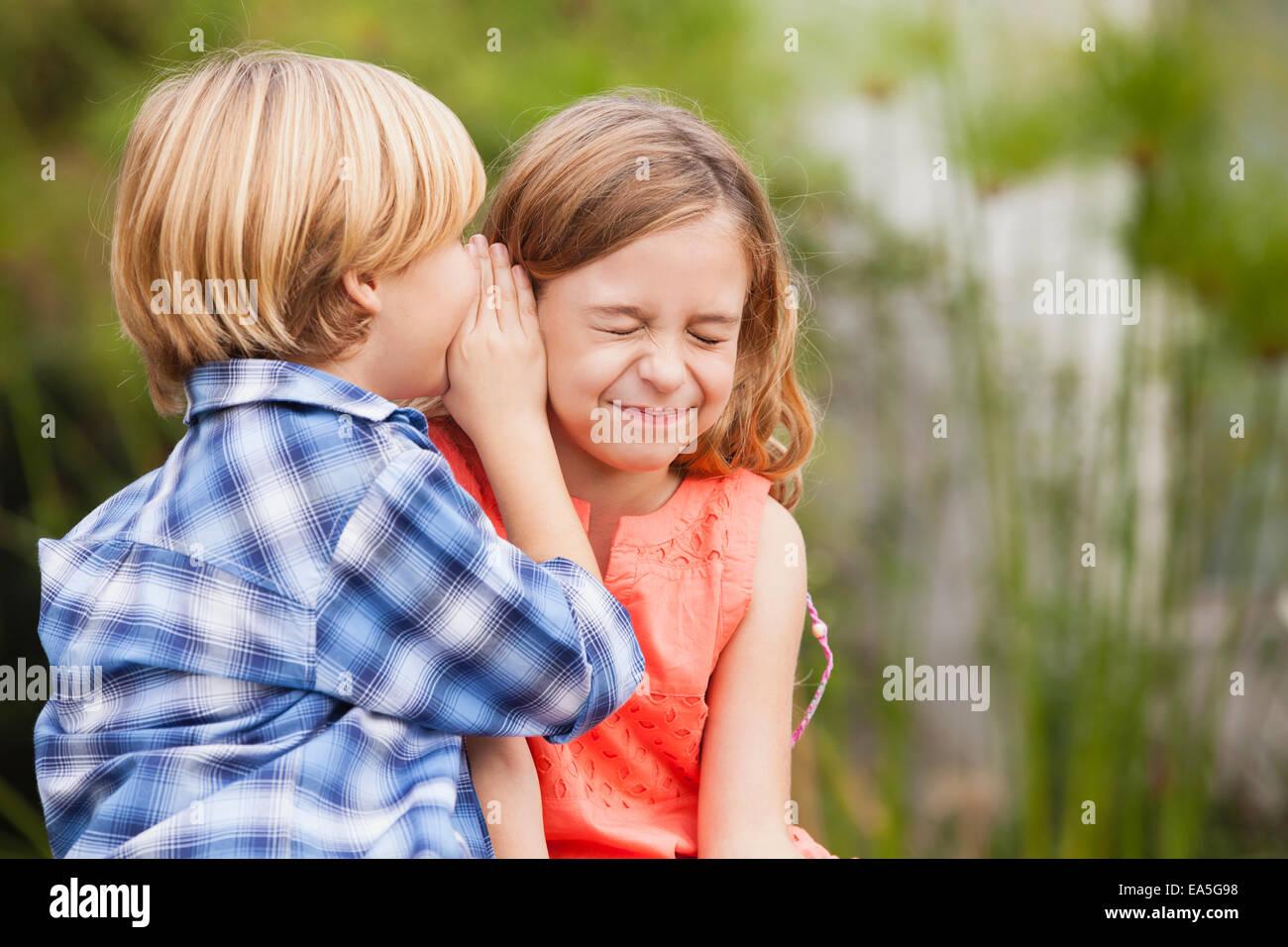 Boy whispering into girl's ear - Stock Image