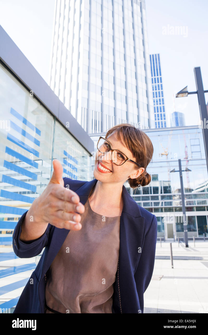 Germany, Hesse, Frankfurt, portrait of greeting businesswoman standing in front of office buildings Stock Photo