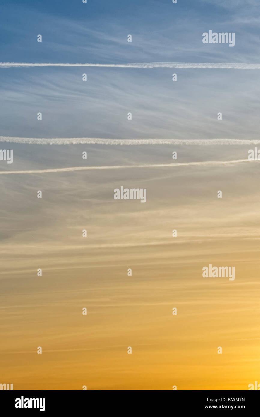 Sunset sky, orange fading to blue; with wispy clouds and contrails. - Stock Image