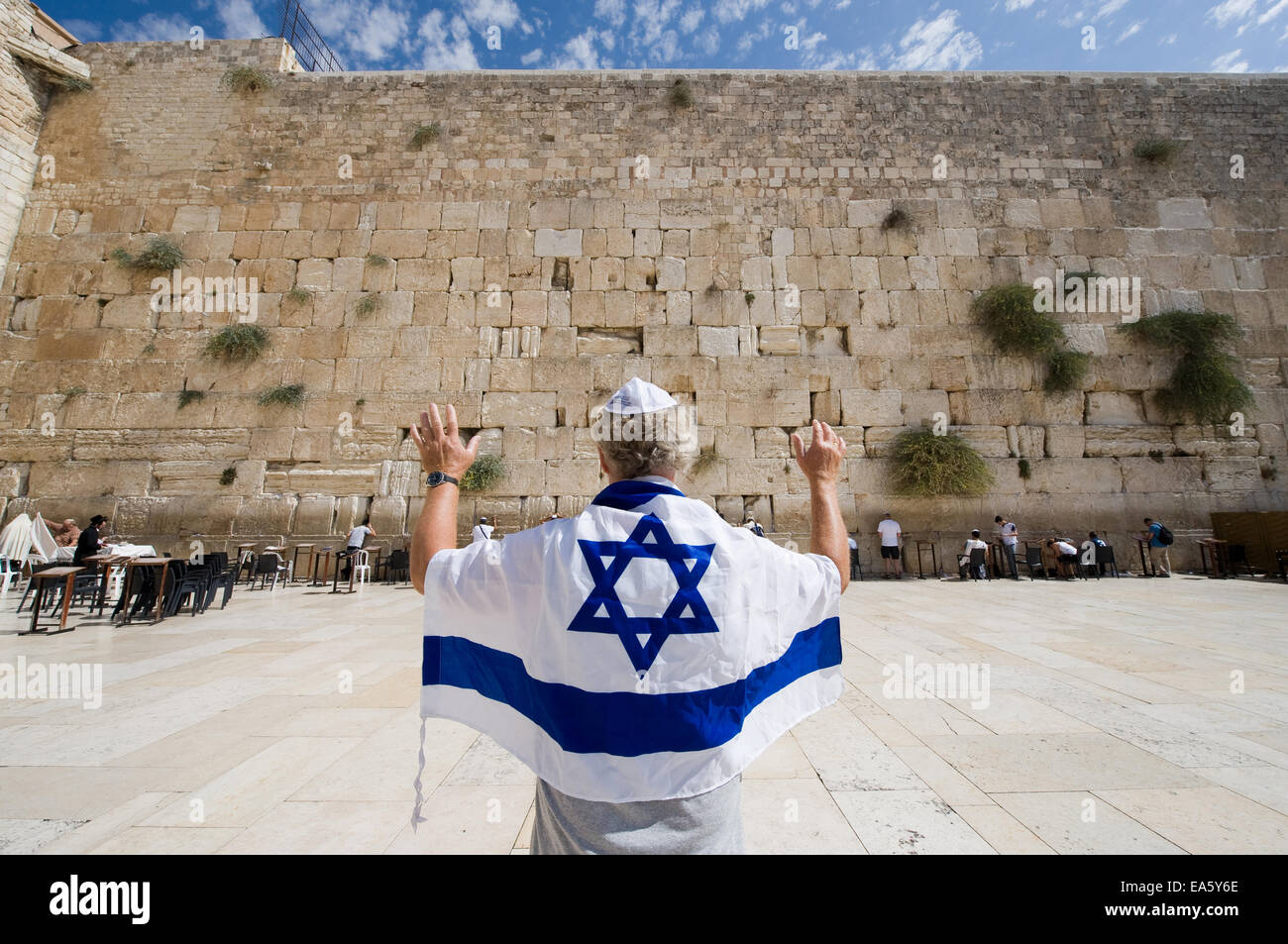 A man with an Israelian flag and his arms raised in front of the western wailing wall in the old city of Jerusalem - Stock Image