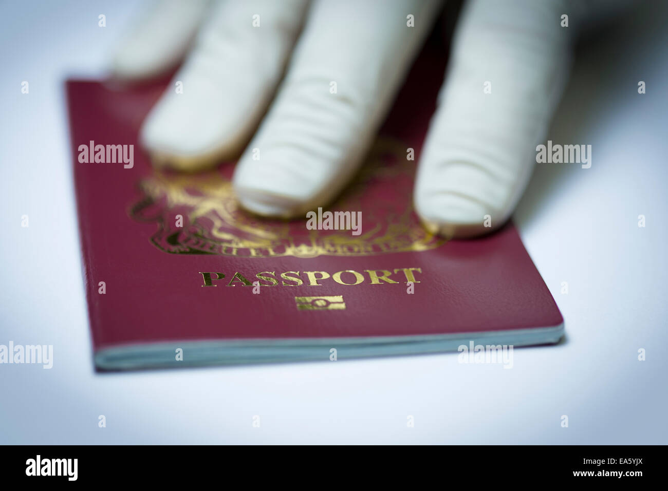 Latex gloved hand returning a passport to its owner. - Stock Image