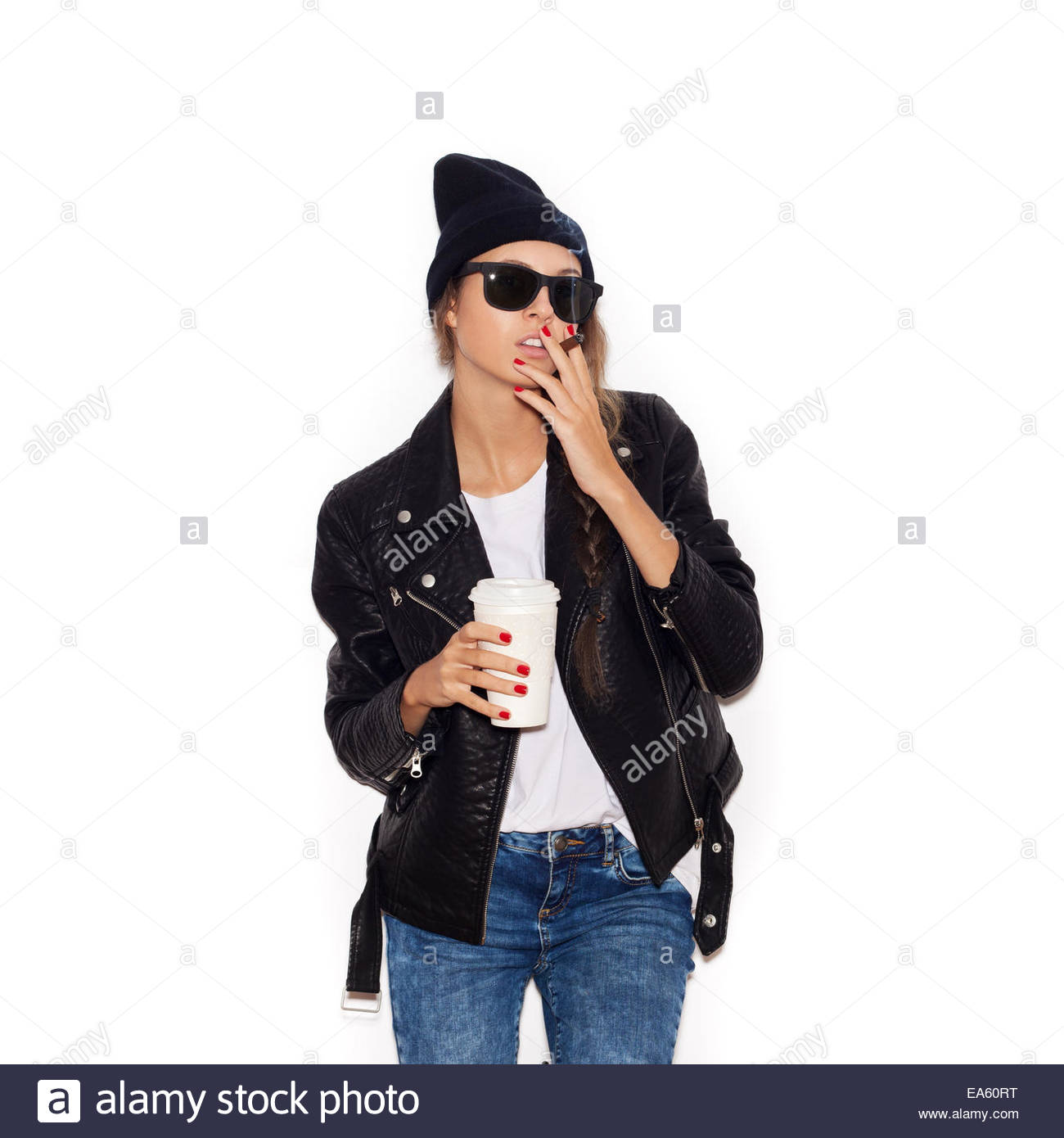 154d814be88 Hipster girl in sunglasses and black beanie smoking cigar. Pretty woman  with cup of coffee. White background