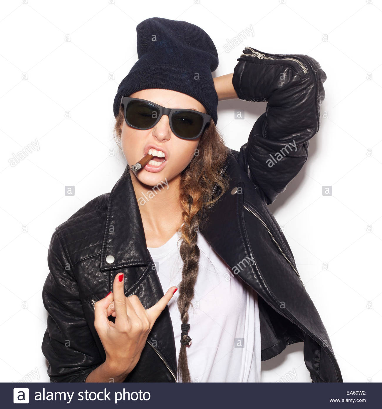 e9ab1467d86 Hipster girl in sunglasses and black beanie smoking and giving the Rock and  Roll sign. White background