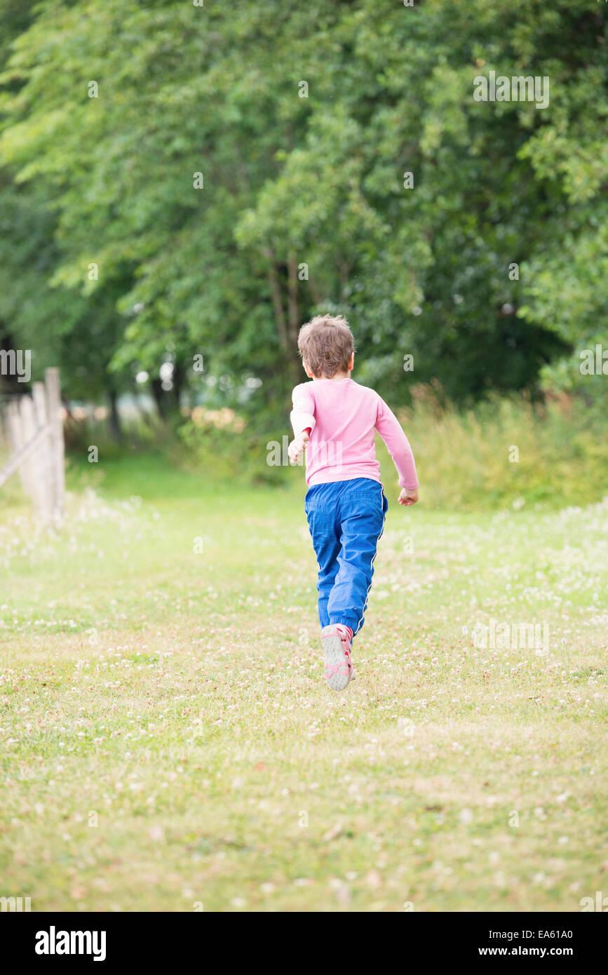 Little girl 4-5 years running in green summer landscape, Sweden - Stock Image