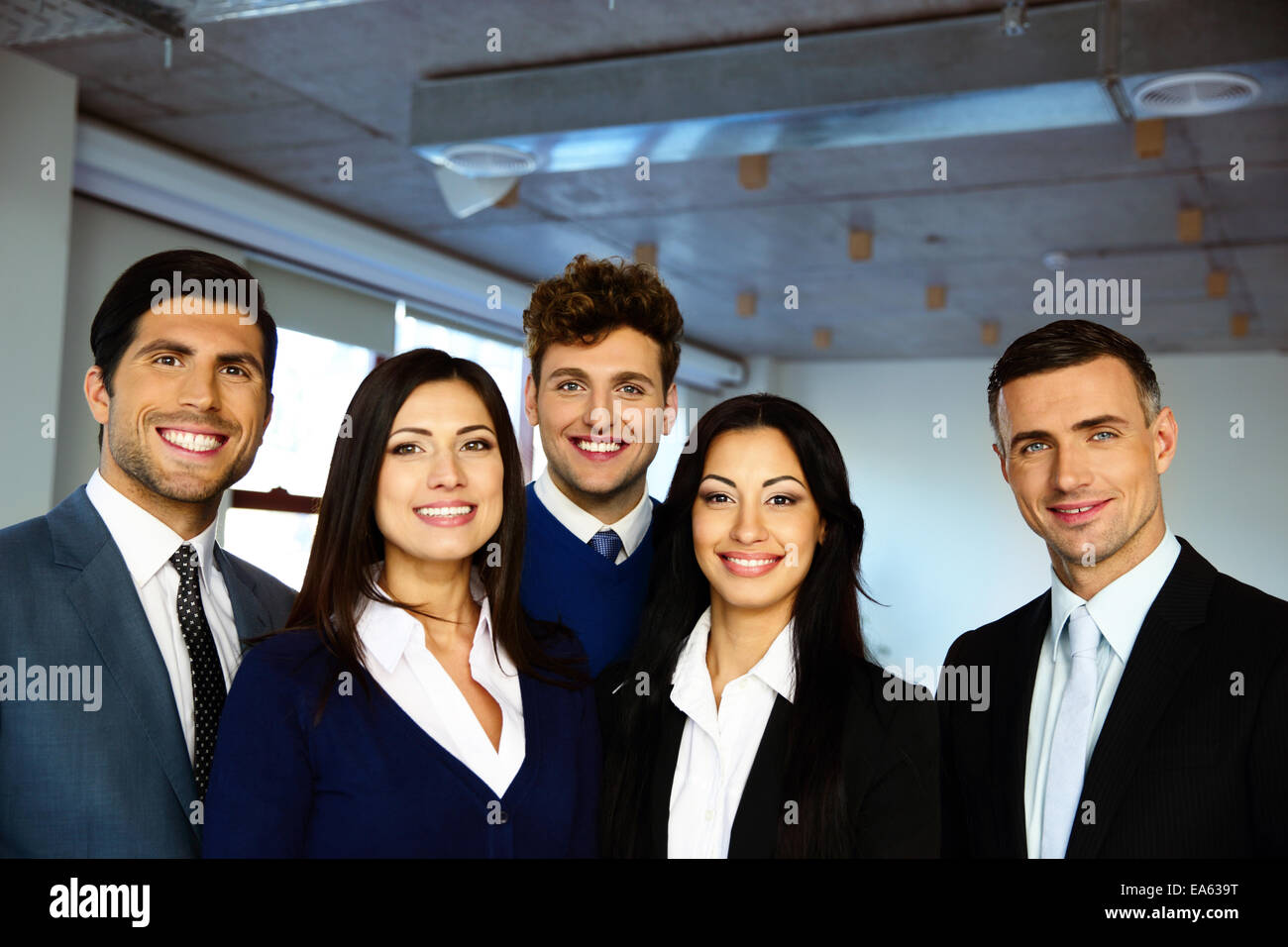 Group of a happy business people standing together in office - Stock Image