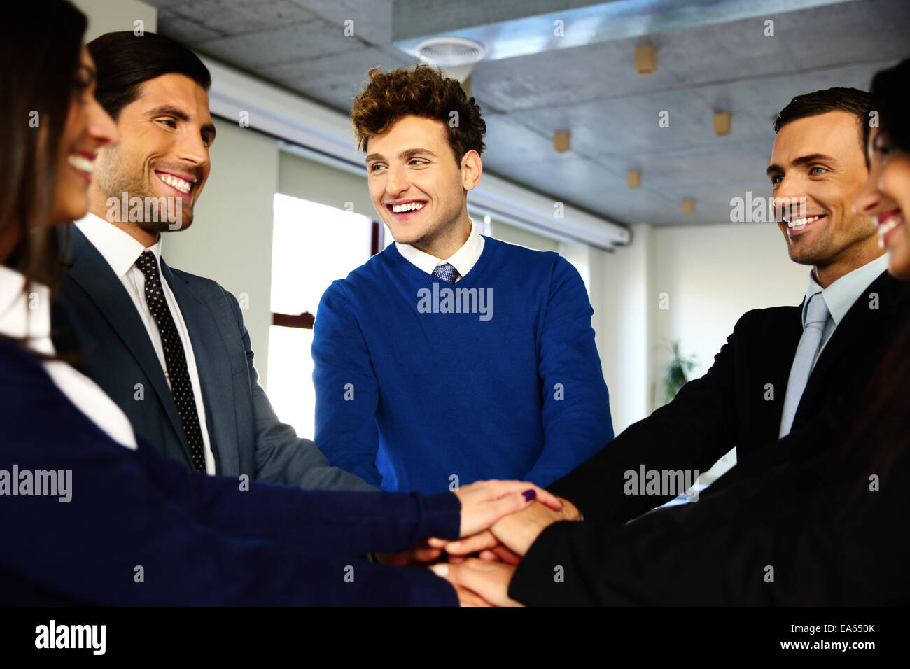 Cheerful co-workers making pile of hands and looking at each other - Stock Image