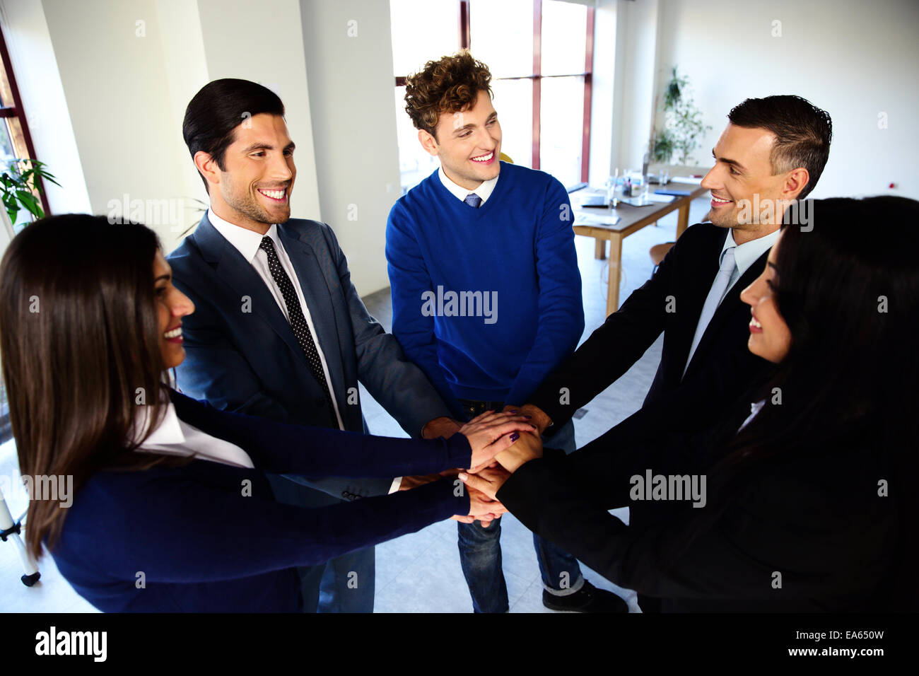 Happy co-workers making pile of hands and looking at each other - Stock Image