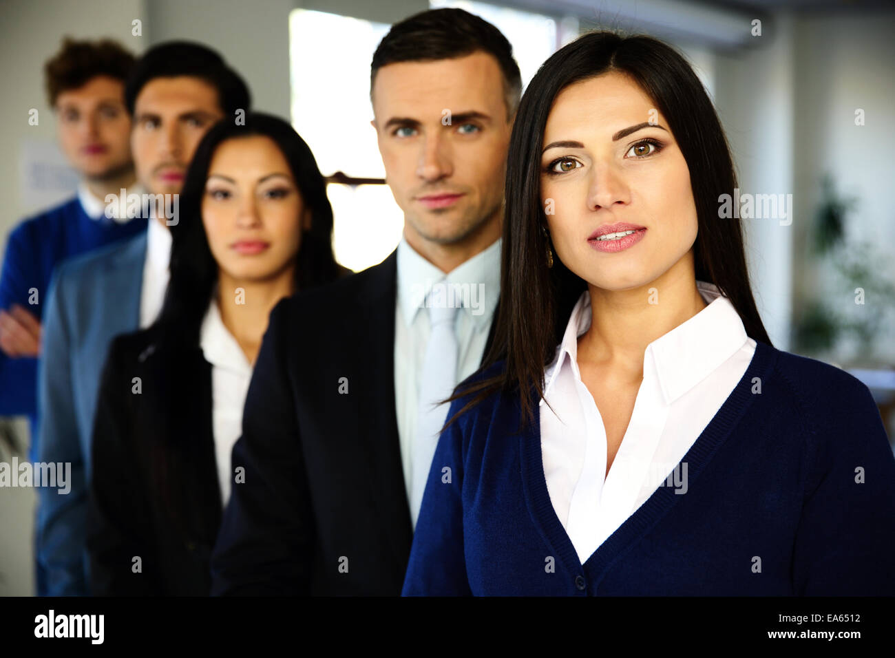 Group of a business people standing lined up in the office - Stock Image