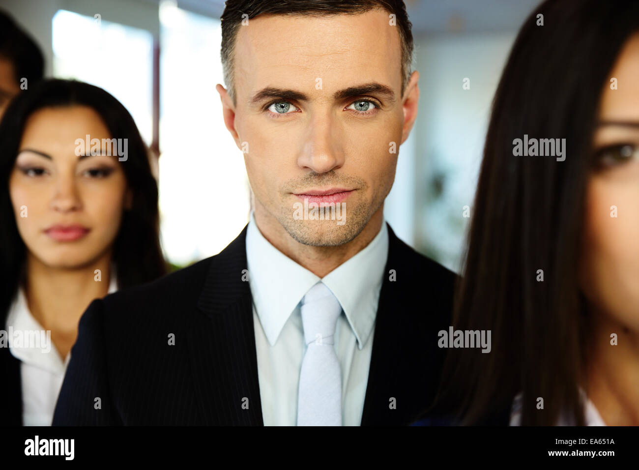 Group of a young businesspeople standing in a row - Stock Image