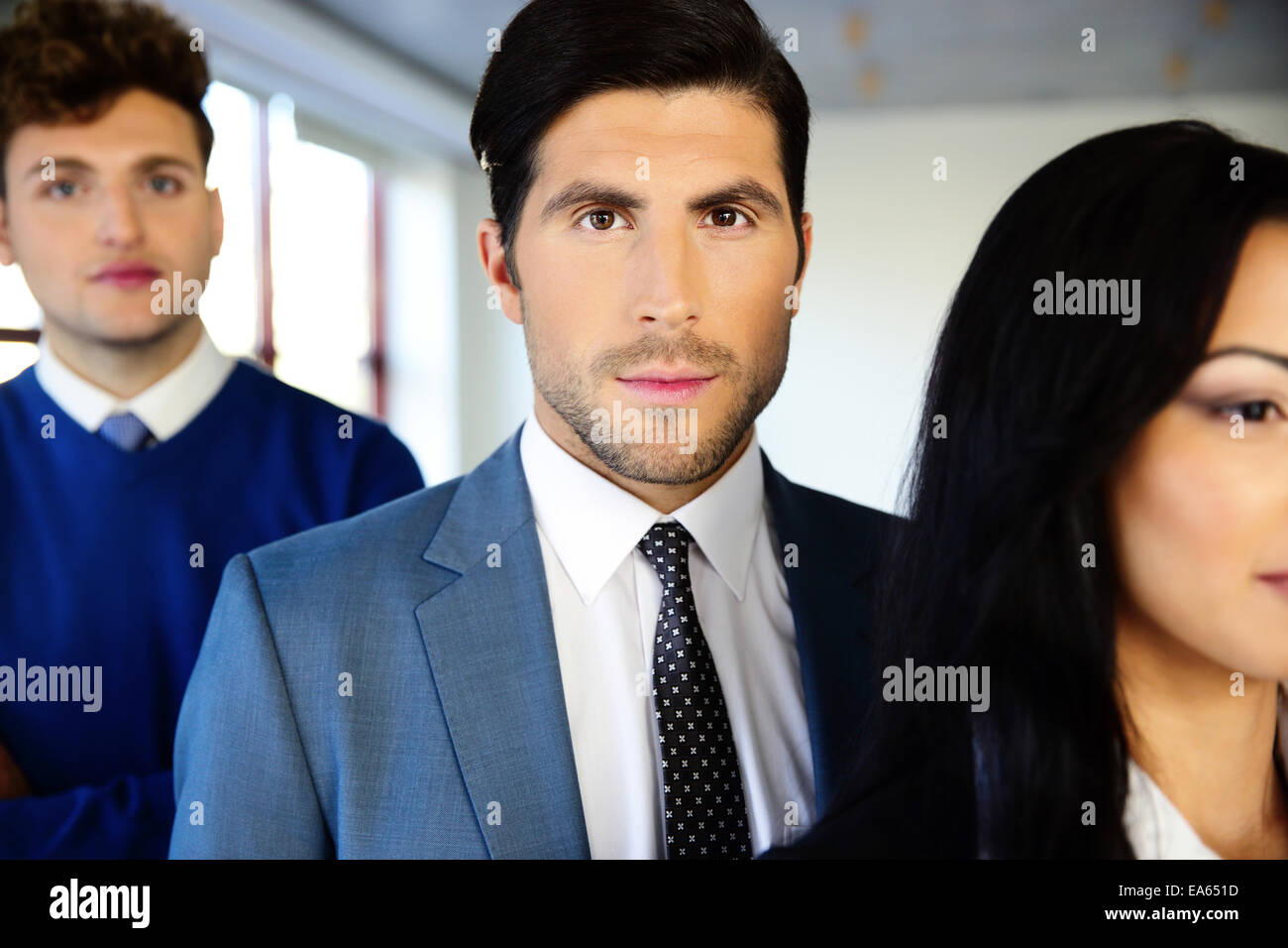 Group of a young serious businesspeople standing in office - Stock Image