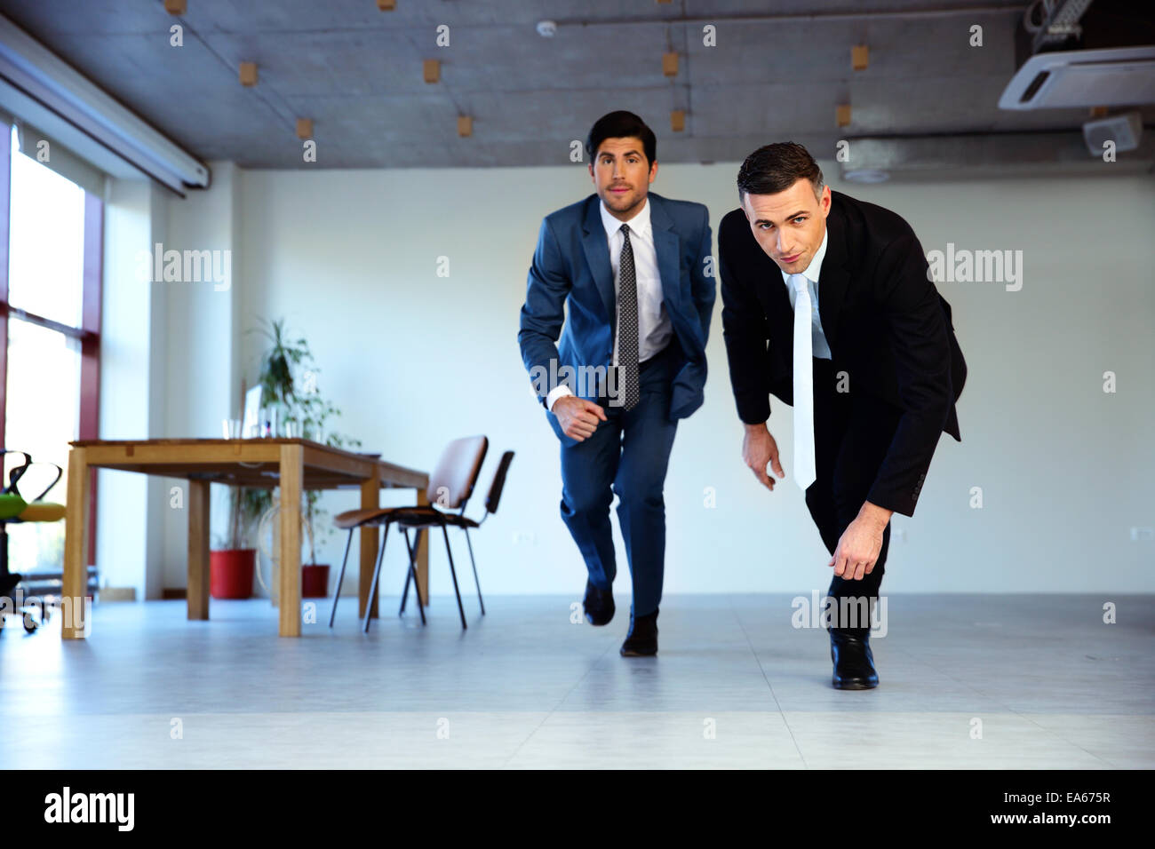 Two businessman running together in office. Business concept Stock Photo