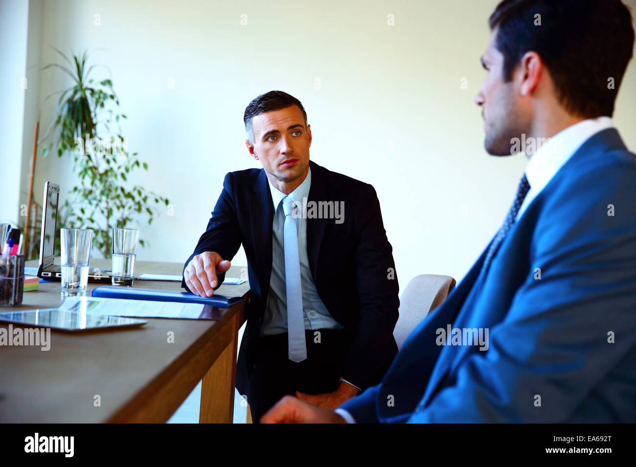 Two businessmen discussing tasks sitting at office table - Stock Image