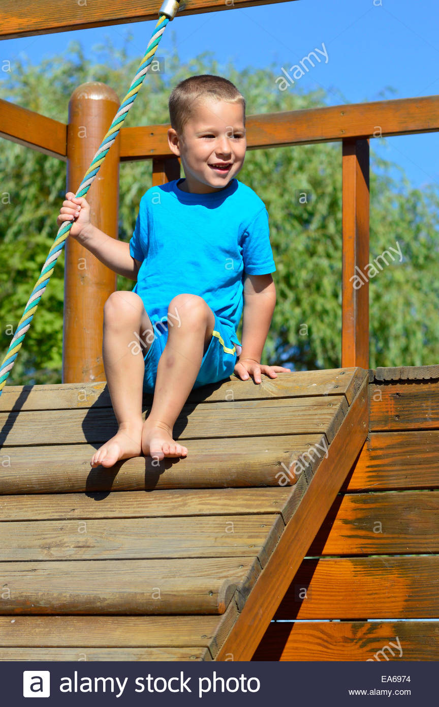 little boy sitting on a climbing tower - Stock Image