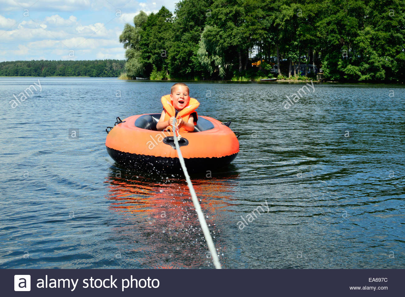 little boy drives a boat - Stock Image