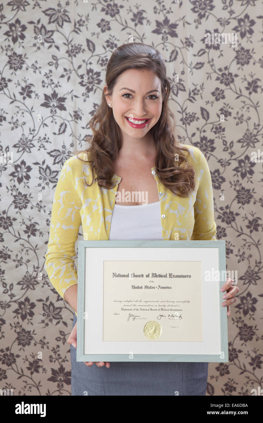 Woman holding framed medical certificate - Stock Image