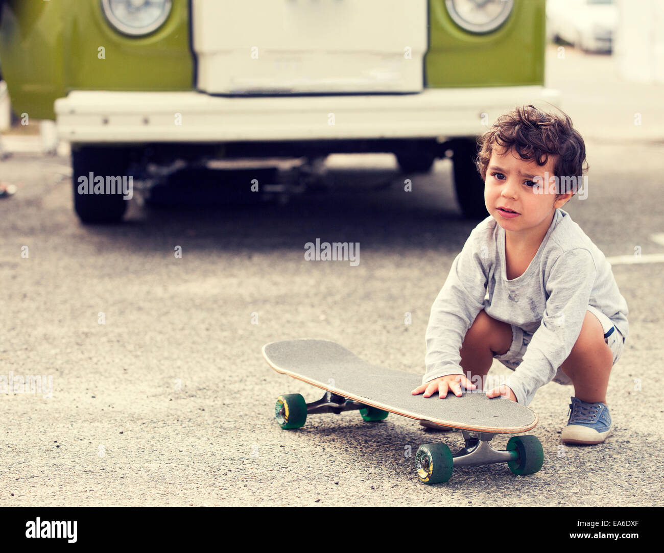 Child with skateboard and van - Stock Image