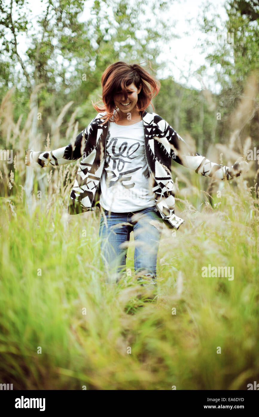 Teenage girl dancing in grass - Stock Image