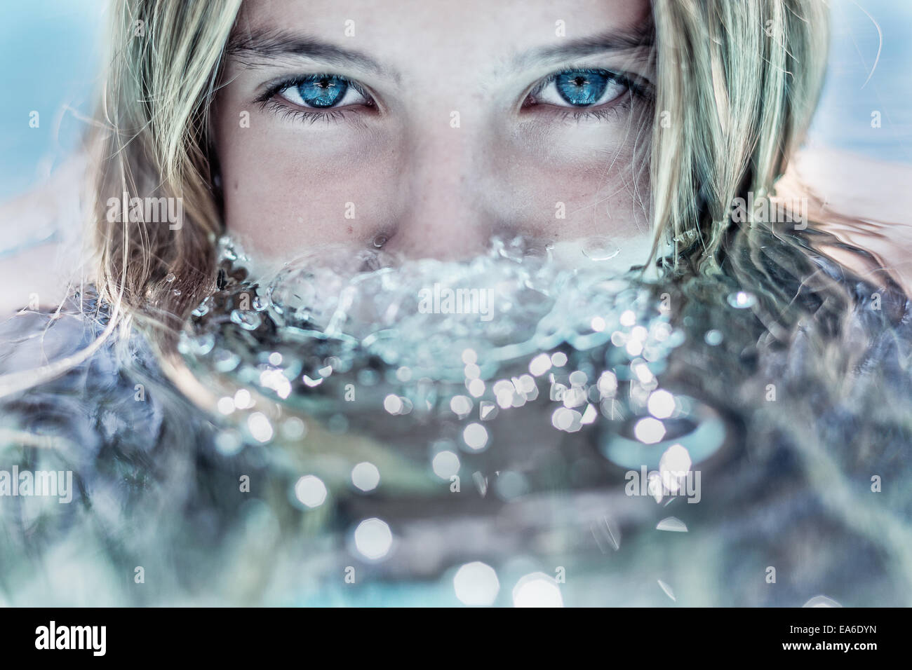 Girl with face partially submerged in water - Stock Image