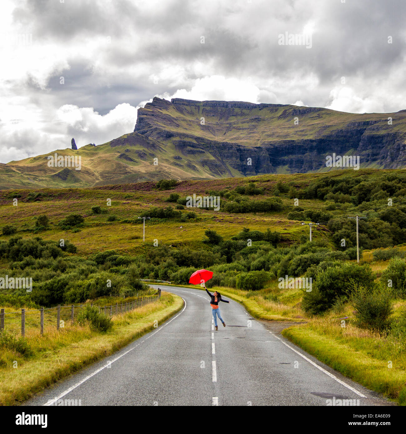 UK, Scotland, Woman with umbrella on country road - Stock Image