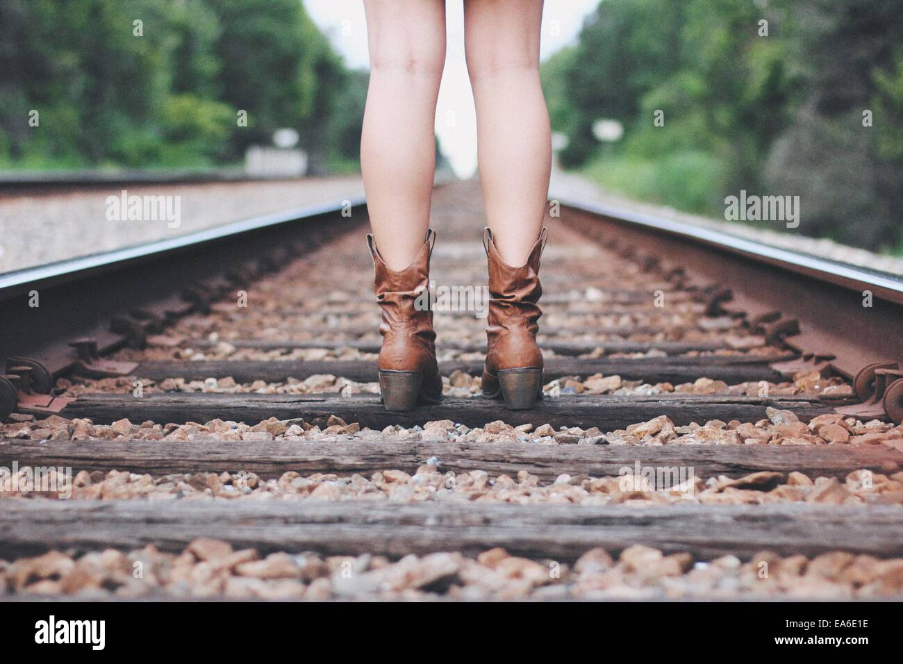 Young woman in boots standing on train tracks - Stock Image