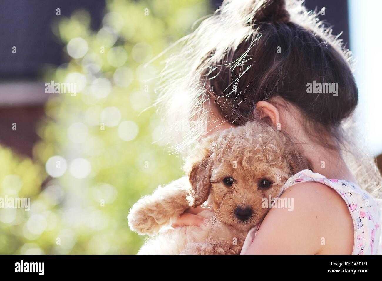 Girl cuddling her puppy dog - Stock Image