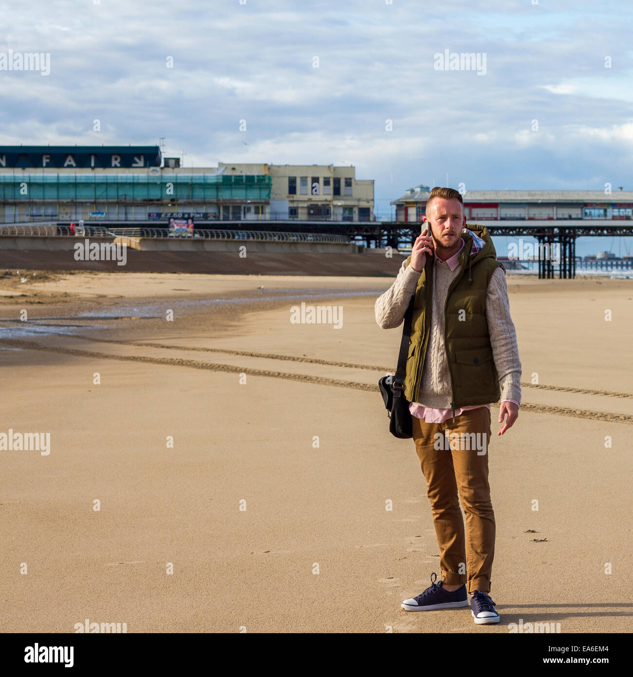 UK, Blackpool, Man with mobile phone on beach - Stock Image