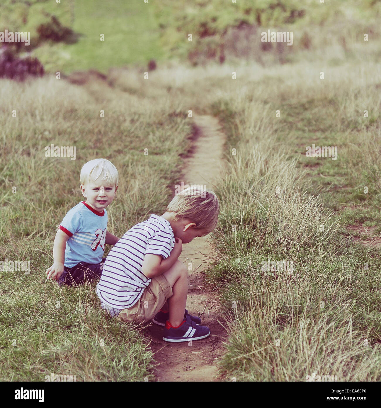 Two boys sitting by a footpath - Stock Image