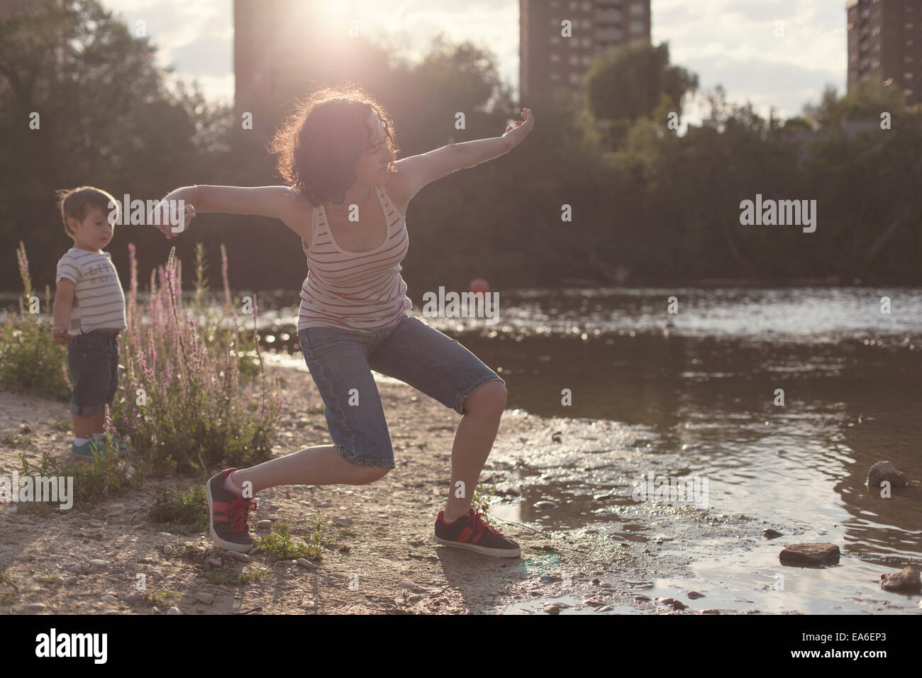 Mother and son standing by a river stone skipping - Stock Image